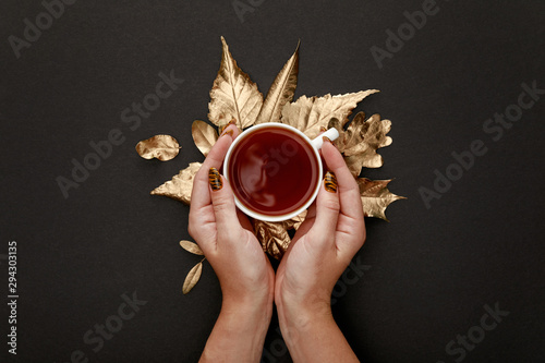 Foto auf AluDibond Natur partial view of woman holding tea in mug near golden foliage on black background