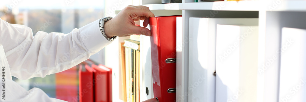 Fototapeta Male arms pick red file folder from office book shelf closeup. Store pile of project documentation concept