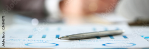 Stampa su Tela Silver pen lie at important paper on table in office closeup with businessman in background