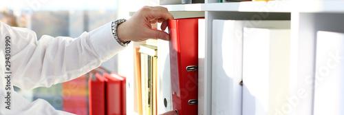 Male arms pick red file folder from office book shelf closeup Fototapet