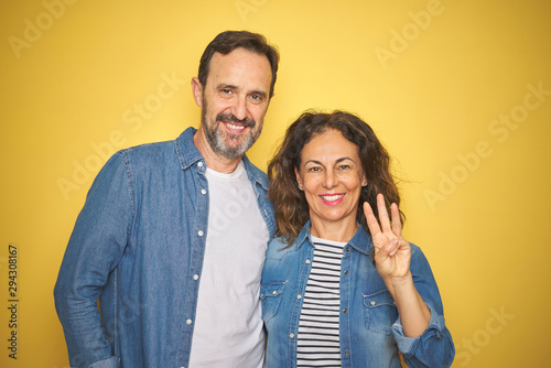 Photo Beautiful middle age couple together wearing denim shirt over isolated yellow background showing and pointing up with fingers number three while smiling confident and happy