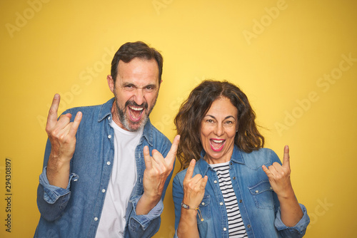 Poster Individuel Beautiful middle age couple together wearing denim shirt over isolated yellow background shouting with crazy expression doing rock symbol with hands up. Music star. Heavy concept.