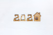 wooden house and number 2020 on a white wooden background. individual construction in the anniversary year