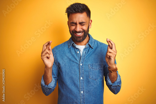 Fotografija Young indian man wearing denim shirt standing over isolated yellow background gesturing finger crossed smiling with hope and eyes closed