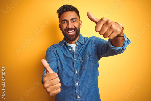 Young indian man wearing denim shirt standing over isolated yellow background approving doing positive gesture with hand, thumbs up smiling and happy for success. Winner gesture.