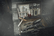 A Set Of Things Hunter Evil Spirits, Demons, Vampires In An Old Suitcase. An Old Book With Spells, Aspen Stakes, Tincture Of Garlic And Holy Water, Rosary, Cross And Gun. The View From The Side.