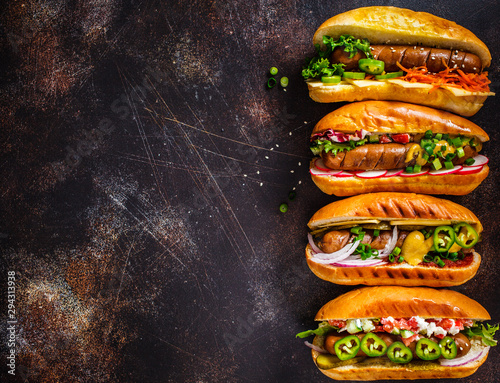 Fotografia Hot dogs with different toppings on dark background, copy space, top view
