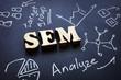 Leinwandbild Motiv SEM letters from wood as abbreviation Search Engine Marketing.