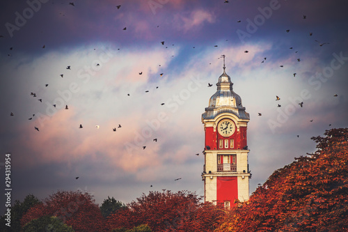 Old tower clock of railway station of Varna city, Bulgaria and flying birds at sunrise.image