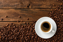 Overhead Shot Of Hot Coffee Cup With Beans On Wooden Background With Copyspace