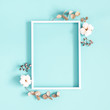 Leinwandbild Motiv Winter composition. Photo frame, dried leaves, cotton flowers, berries on blue background. Autumn, winter concept. Flat lay, top view, copy space, square
