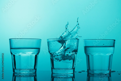 Photo sur Toile Alcool Three glasses with clear water and splashes on blue background
