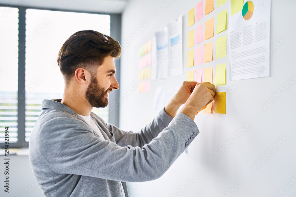 Fototapeta Young entrepreneur sticking note to wall in office