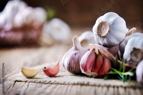 Fototapeta Garlic cloves on rustic table. Garlic in wooden bowl. Fresh peeled garlic and  bulbs. obraz
