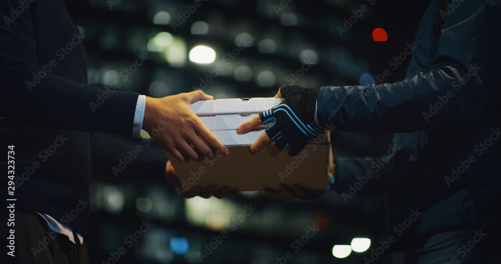 Fototapety, obrazy: Close up of an young pizza courier is delivering an order to a customer in the evening in a city center.