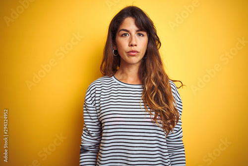 Young beautiful woman wearing stripes t-shirt standing over yelllow isolated background Relaxed with serious expression on face. Simple and natural looking at the camera.