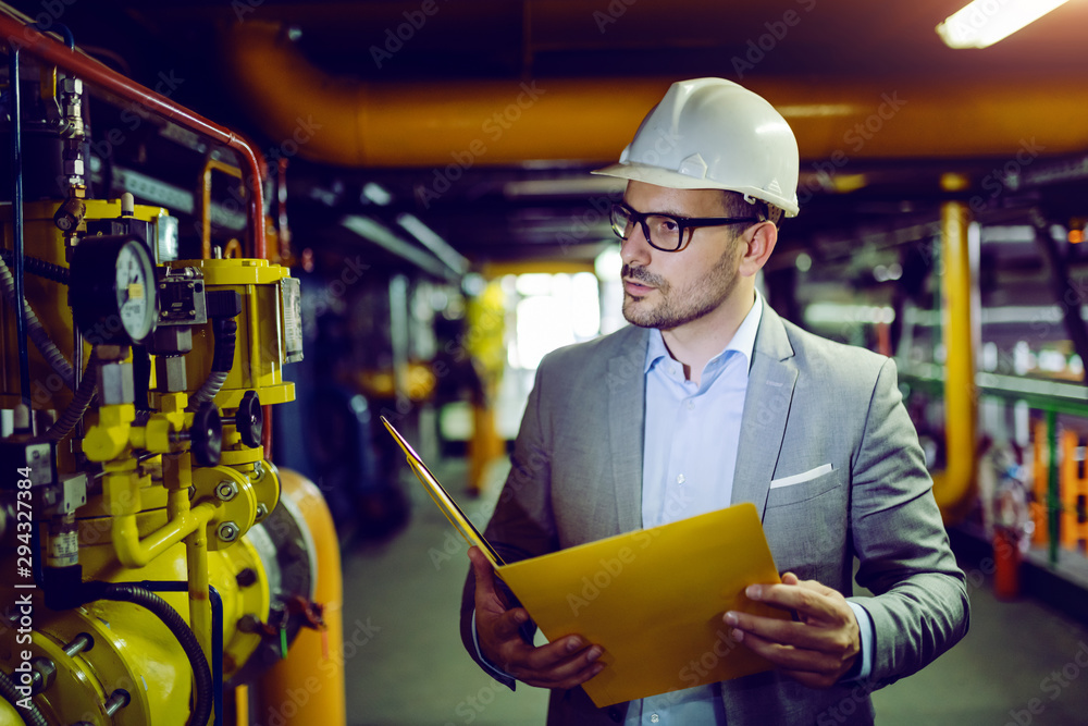 Fototapeta Serious caucasian supervisor in suit and with helmet on head holding folder with documents and looking at thermostat.