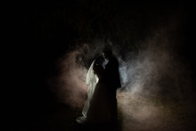 Silhouette Of A Bride And Groom At Night With A Smokey Background