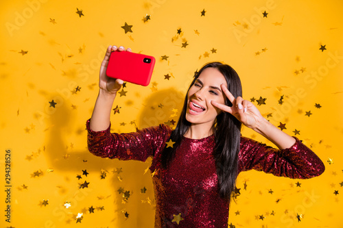 Close-up portrait of nice attractive charming glamorous cheery girl holding in hands cell making selfie showing v-sign tongue out fooling isolated on bright vivid shine vibrant yellow color background