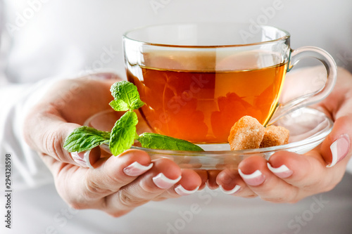 Tuinposter Thee Woman holding cup of green tea in glass cup. Hot tea with mint leaf in glass jar or cup.