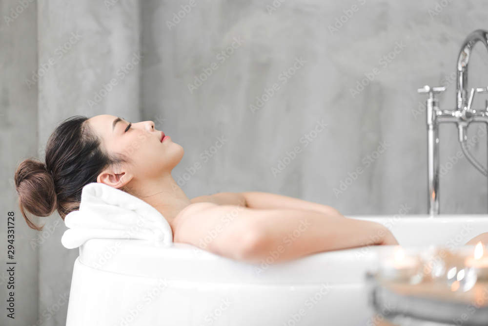 Fototapeta Beautiful young asia woman enjoy relaxing taking a bath with bubble foam in bathtub at the bathroom