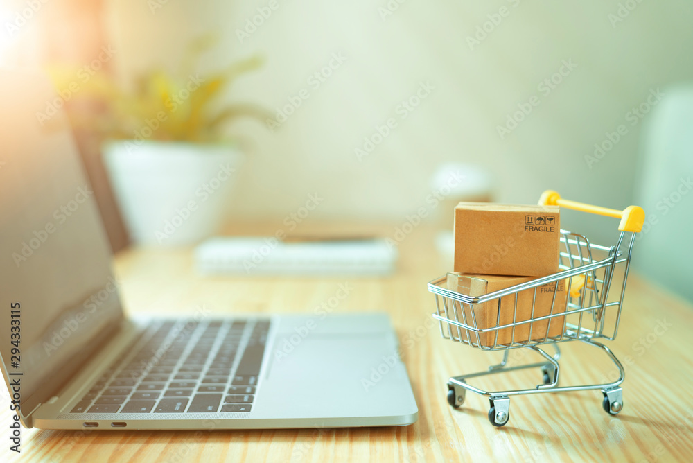 Fotografia Brown paper boxs in a shopping cart with laptop keyboard on wood table in office background