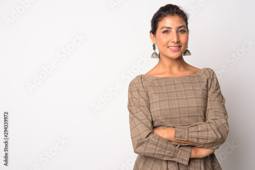 Happy young beautiful Persian woman smiling with arms crossed