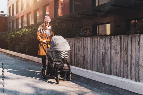 Young woman with baby stroller walking down city streets Tablou Canvas