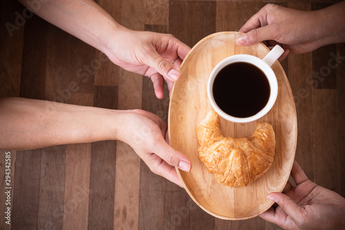 Close up woman hand serving hot black coffee and croissant on wooden plate in coffee shop.Cafe drinking menu hot coffee at restaurant.Breakfast menu in the morning time.
