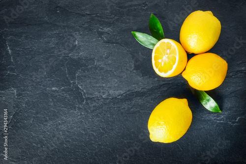Fresh lemons on dark stone table. Ripe lemon from top view with green leaves. Fresh ripe lepon concept. - 294343164