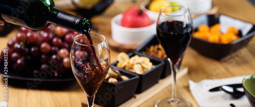 Stampa su Tela  Pouring wine into glass and food background