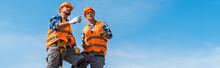 Panoramic Shot Of Coworkers In Orange Helmets Standing On Rocks Against Sky
