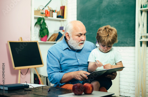Obraz Teacher and pupil learning together in school. Educational process. Grandfather with grandson learning together. - fototapety do salonu