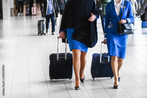 Foto Two stewardess walk on airport station with suitcases in blue.