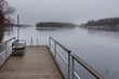 Small pier at beach on Lake Ruotsalainen at cloudy, winter day, Finland.