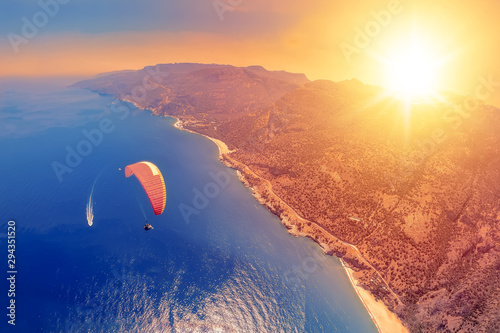 Foto auf AluDibond Koralle Extreme sport. Landscape . Paragliding in the sky. Paraglider tandem flying over the sea with blue water and mountains in bright sunny day. Aerial view of paraglider and Blue Lagoon in Oludeniz, Turke