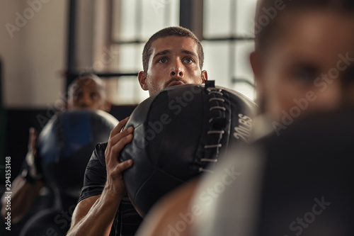 Fitness man doing squat with heavy ball Canvas-taulu