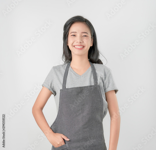 Fotografía Asian woman in apron and standing and looking forward on gray background