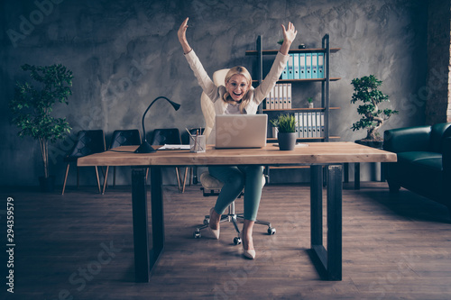 Photo of cheerful smiling entrepreneur having finally finished working on her project and is now able to have some rest sitting in front of her laptop