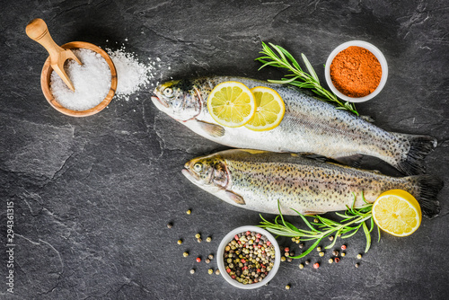 Valokuvatapetti Fresh trout on dark table with salt pepper and rosemary