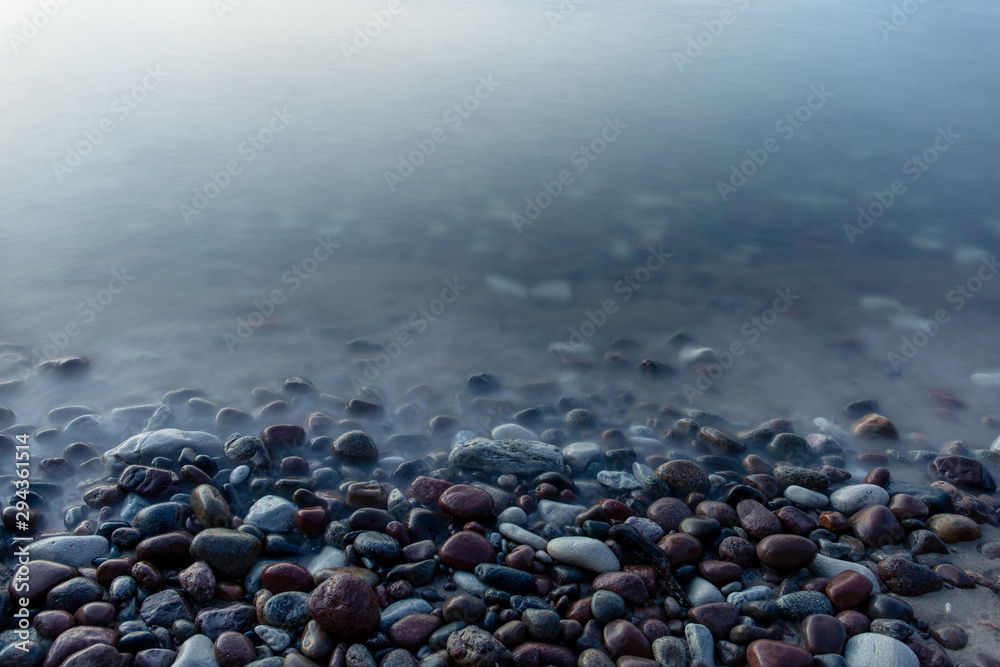 Fototapety, obrazy: multi-colored smooth stones by the sea at a long exposure in twilight