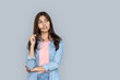 Curious young adult indian woman standing isolated on grey background with copy space. Dreaming girl in denim wear looking away holding glasses in hand uncertain with question interested or doubting