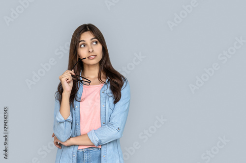 Curious young adult indian woman standing isolated on grey background with copy space Wallpaper Mural