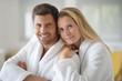 Leinwandbild Motiv Young casual couple in white bathrobe