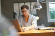 Leinwanddruck Bild - Middle-aged man working on laptop in office