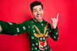 canvas print picture - Portrait of funky funny crazy man in deer reindeer sweater make selfie show horned sign scream true rock-and roll heavy metal hipster on christmas event isolated over red color background