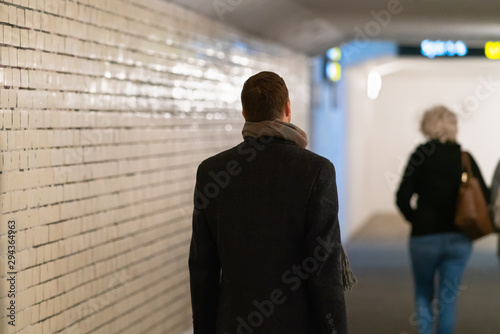 Man in overcoat following a woman in subway Canvas-taulu