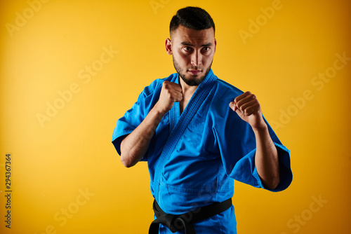Asian Kazakh karate fighter in kimono uniform is combat on yellow background wit Wallpaper Mural