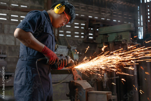 Fototapeta Engineer operating angle grinder hand tools in manufacturing factory - Mechanica