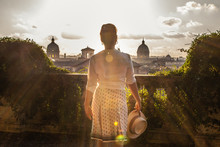 Young Woman Tourist In Fashion White Dress With Hat At Panoramic View Of Rome Cityscape From Campidoglio Terrace At Sunset. Landmarks, Domes Of Rome, Italy.